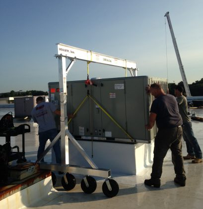 EC&MWs 2TAC1212 Model air tire gantry crane. Worker are moving a roof top air handler